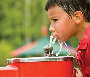 Child drinking water from fountain